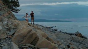 Νεαρός άνδρας και γυναίκα που τρέχουν κατά μήκος της ακτής στο θερινό βράδυ υπαίθρια απόθεμα βίντεο