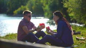 Νεαρός άνδρας και γυναίκα που τρώνε το καρπούζι στο πικ-νίκ στο δάσος κοντά στον ποταμό στο υπόβαθρο των βουνών 4 Κ φιλμ μικρού μήκους