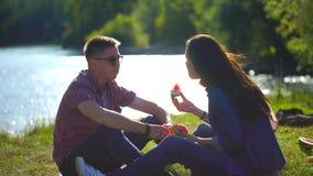 Νεαρός άνδρας και γυναίκα που τρώνε το καρπούζι στο πικ-νίκ στο δάσος κοντά στον ποταμό στο υπόβαθρο των βουνών 4 Κ απόθεμα βίντεο
