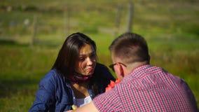 Νεαρός άνδρας και γυναίκα που τρώνε το καρπούζι στο πικ-νίκ στο δάσος κοντά στον ποταμό 4 Κ απόθεμα βίντεο