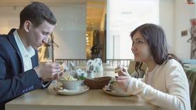 Νεαρός άνδρας και γυναίκα σε έναν καφέ πρακτικό μεσημεριανό γεύμα ζητημάτων φλυτζανιών επιχειρησιακού καφέ που ανοίγουν απόθεμα βίντεο