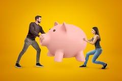 Νεαρός άνδρας και γυναίκα στα περιστασιακά ενδύματα που κρατούν τη μεγάλη ρόδινη piggy τράπεζα στο κίτρινο υπόβαθρο στοκ φωτογραφίες
