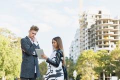 Νεαρός άνδρας και κορίτσι στην οδό που εξετάζει την ταμπλέτα Στοκ φωτογραφίες με δικαίωμα ελεύθερης χρήσης