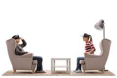 Νεαρός άνδρας και μια νέα γυναίκα που κάθεται σε χρησιμοποίηση πολυθρόνων εικονική σχετικά με Στοκ Εικόνα