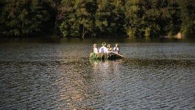 Νεαρός άνδρας και τρία όμορφα κορίτσια στα στεφάνια και τα κεντημένα πουκάμισα επιπλέουν σε μια βάρκα στον ποταμό σλαβικός φιλμ μικρού μήκους