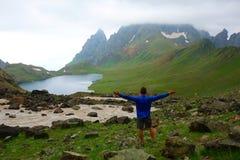 Νεαρός άνδρας μετά από να διασχίσει ένα χιονώδες πέρασμα βουνών που οδηγεί στη λίμνη Tobavarchkhili στα βουνά Καύκασου στη Γεωργί στοκ εικόνα με δικαίωμα ελεύθερης χρήσης
