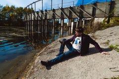 Νεαρός άνδρας με μια γενειάδα ένα ταξίδι στη λίμνη, ένα εγκαταλειμμένο παλαιό φράγμα, μια θερμή ηλιόλουστη ημέρα Στοκ φωτογραφίες με δικαίωμα ελεύθερης χρήσης