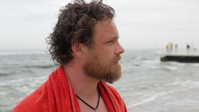 Νεαρός άνδρας με μια γενειάδα και ένα υγρό κεφάλι με μια πετσέτα στους ώμους του στα πλαίσια της θάλασσας μετά από να κολυμπήσει  απόθεμα βίντεο