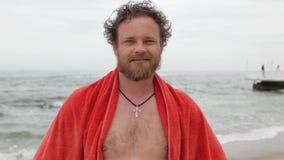 Νεαρός άνδρας με μια γενειάδα και μπλε μάτια στο υπόβαθρο της θάλασσας με μια πετσέτα στους ώμους του που χαμογελούν εξετάζοντας  απόθεμα βίντεο