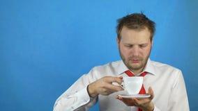 Νεαρός άνδρας με μια γενειάδα που φορά έναν άσπρο καφέ κατανάλωσης πουκάμισων και δεσμών με μια απόλυση και μια υπνηλία, μπλε υπό απόθεμα βίντεο