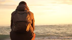 Νεαρός άνδρας με μια συνεδρίαση σακιδίων πλάτης στην ακτή και την εξέταση τα κύματα στη θάλασσα απόθεμα βίντεο