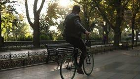 Νεαρός άνδρας με τα ακουστικά που οδηγούν το ποδήλατο στο πάρκο στο μαύρο ποδήλατο οδοιπορίας Οδήγηση με τα nohands ακούοντας  φιλμ μικρού μήκους