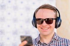 Νεαρός άνδρας με τα ακουστικά bluetooth που συνδέονται με το smartphone στοκ φωτογραφίες