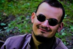 Νεαρός άνδρας με τα γυαλιά ηλίου και το τρελλό χαμόγελο Στοκ Εικόνα