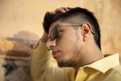 Νεαρός άνδρας με τα γυαλιά ηλίου που σκέφτεται την κλίση σε έναν τοίχο στοκ φωτογραφίες με δικαίωμα ελεύθερης χρήσης
