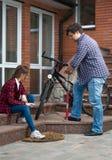 Νεαρός άνδρας με την κόρη που επισκευάζει το ποδήλατο και που αντλεί τις ρόδες Στοκ Φωτογραφία