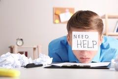Νεαρός άνδρας με τη ΒΟΗΘΕΙΑ ΑΝΑΓΚΗΣ σημειώσεων στο μέτωπο στον εργασιακό χώρο στοκ εικόνα με δικαίωμα ελεύθερης χρήσης