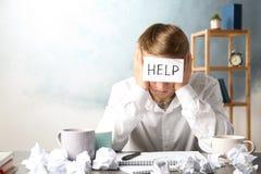 Νεαρός άνδρας με τη ΒΟΗΘΕΙΑ σημειώσεων στο μέτωπο στον εργασιακό χώρο στοκ εικόνα