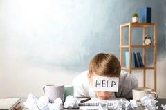 Νεαρός άνδρας με τη ΒΟΗΘΕΙΑ σημειώσεων στο μέτωπο στον εργασιακό χώρο στοκ εικόνες