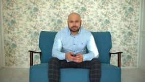 Νεαρός άνδρας με τη μακρινή TV προσοχής TV στον καναπέ φιλμ μικρού μήκους