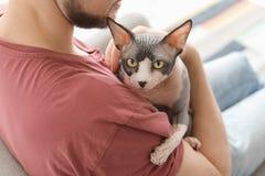 Νεαρός άνδρας με τη χαριτωμένη γάτα στοκ εικόνα