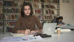 Νεαρός άνδρας με τις μακρυμάλλεις κάνοντας σημειώσεις στη συνεδρίαση σημειωματάριων στη βιβλιοθήκη απόθεμα βίντεο