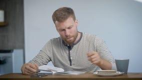 Νεαρός άνδρας με τον καφέ κατανάλωσης γενειάδων και ανάγνωση του περιοδικού στην κουζίνα το πρωί απόθεμα βίντεο