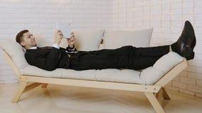 Νεαρός άνδρας με τον υπολογιστή ταμπλετών στον καναπέ φιλμ μικρού μήκους