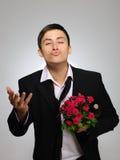 Νεαρός άνδρας με το ροδαλό μπουκάλι λουλουδιών και αμπέλων Στοκ Φωτογραφία