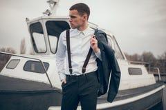 Νεαρός άνδρας με το σακάκι στις στάσεις χεριών του στην αποβάθρα δίπλα στη βάρκα στοκ φωτογραφίες