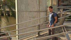 Νεαρός άνδρας με το σακίδιο πλάτης που περπατά κάτω σε μια βιασύνη, σπουδαστής που πηγαίνει στις κατηγορίες φιλμ μικρού μήκους