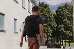Νεαρός άνδρας με το σακίδιο πλάτης που περπατά στο σχολείο μετά από τις καλοκαιρινές διακοπές στοκ εικόνα
