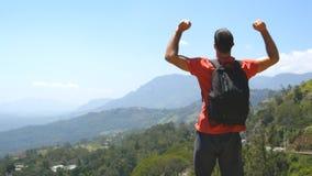 Νεαρός άνδρας με το σακίδιο πλάτης που φθάνει επάνω στην κορυφή του βουνού και των αυξημένων χεριών Αρσενικός τουρίστας που στέκε απόθεμα βίντεο