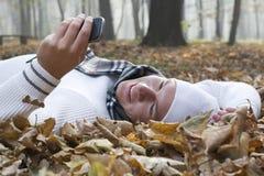 Νεαρός άνδρας με το χαμόγελο και τηλέφωνο της Mobil στο autumun Στοκ εικόνα με δικαίωμα ελεύθερης χρήσης