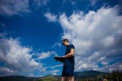 Νεαρός άνδρας με το lap-top και την εργασία Στοκ Εικόνες