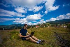 Νεαρός άνδρας με το lap-top και την εργασία Στοκ εικόνα με δικαίωμα ελεύθερης χρήσης
