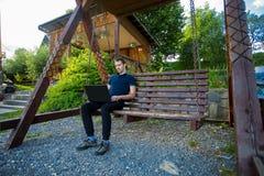 Νεαρός άνδρας με το lap-top και την εργασία Στοκ φωτογραφίες με δικαίωμα ελεύθερης χρήσης
