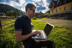 Νεαρός άνδρας με το lap-top και την εργασία Στοκ εικόνες με δικαίωμα ελεύθερης χρήσης