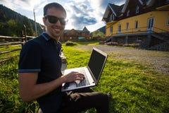 Νεαρός άνδρας με το lap-top και την εργασία Στοκ φωτογραφία με δικαίωμα ελεύθερης χρήσης