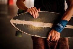 Νεαρός άνδρας με armband που κρατά ένα longboard Στοκ φωτογραφία με δικαίωμα ελεύθερης χρήσης