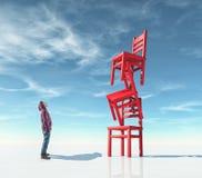 Νεαρός άνδρας μπροστά από τις καρέκλες στην ισορροπία ελεύθερη απεικόνιση δικαιώματος