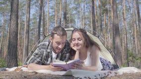 Νεαρός άνδρας πορτρέτου και αρκετά νέα γυναίκα που βρίσκονται η μια κοντά στην άλλη στη σκηνή στη δασική ανάγνωση το βιβλίο Αγάπη απόθεμα βίντεο