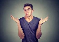 Νεαρός άνδρας πορτρέτου κινηματογραφήσεων σε πρώτο πλάνο που απαξιεί τους ώμους Γλώσσα του σώματος στοκ φωτογραφία