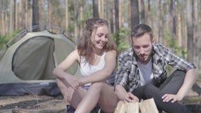Νεαρός άνδρας πορτρέτου που ανάβει μια πυρκαγιά στο δάσος ενώ λατρευτή νέα συνεδρίαση γυναικών πλησίον Αγαπώντας ζεύγος που στηρί απόθεμα βίντεο