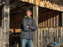 Νεαρός άνδρας πορτρέτου που στέκεται στο ξύλινο κτήριο με τα thermos και το μπλε φλυτζάνι στοκ εικόνες