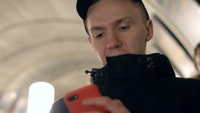 Νεαρός άνδρας πορτρέτου που χρησιμοποιεί το κινητό τηλέφωνο για τα δίκτυα ξεφυλλίσματος στο escalato μετρό απόθεμα βίντεο