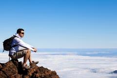 Νεαρός άνδρας που έχει ένα υπόλοιπο σε μια υψηλή αιχμή πέρα από τα σύννεφα στοκ φωτογραφίες