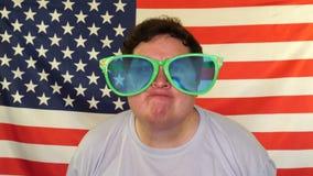 Νεαρός άνδρας που έχει τη διασκέδαση στα τεράστια γυαλιά ηλίου φιλμ μικρού μήκους