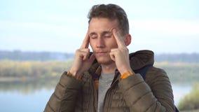Νεαρός άνδρας που αισθάνεται την ισχυρή έννοια επίθεσης πονοκέφαλου, εξαντλημένος κουρασμένος τύπος που τρίβει τους ναούς για να  απόθεμα βίντεο