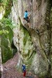Νεαρός άνδρας που αναρριχείται στον κάθετο απότομο βράχο, συνεργατών του Στοκ Φωτογραφία